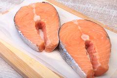 Fresh raw salmon with spices on wooden cutting board. ready for cookin Royalty Free Stock Photos