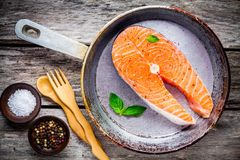 Fresh raw salmon steak on cast-iron pan with sea salt and peppers. On the rustic wooden table Stock Image