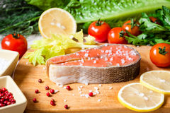 Fresh raw salmon steak on cutting board with salt and pink pepper. Selective focus Royalty Free Stock Image