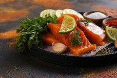 Fresh raw salmon steak. On dark background. Cooking or grill concept. Space for text Stock Image