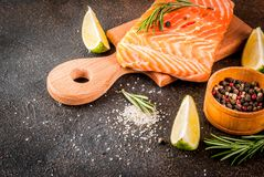 Fresh raw salmon steak fillet. Fresh raw fish salmon, steak fillet, with spices, lime, rosemary, salt, on a dark rusty background, copy space Royalty Free Stock Photo