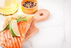 Fresh raw salmon steak fillet. Fresh raw fish salmon, steak fillet, with spices, lime, rosemary, salt, on white marble background, copy space Royalty Free Stock Photography