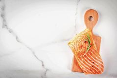 Fresh raw salmon steak fillet. Fresh raw fish salmon, steak fillet, with spices, lime, rosemary, salt, on white marble background, copy space top view Royalty Free Stock Photos