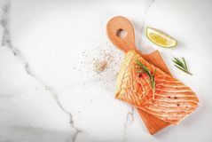 Fresh raw salmon steak fillet. Fresh raw fish salmon, steak fillet, with spices, lime, rosemary, salt, on white marble background, copy space top view Stock Image