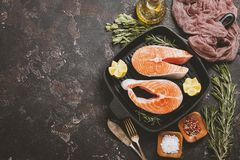 Fresh raw salmon steak. Lemon, rosemary and spices on grill frying pan over dark rustic concrete background, top view with copy space. Ingredients set for Stock Photography