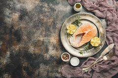 Fresh raw salmon steak. Lemon, rosemary and spices on metal plate over dark rustic concrete background, top view with copy space. Ingredients set for making Royalty Free Stock Photo