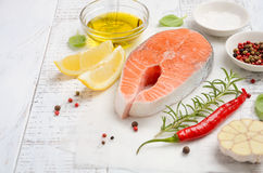 Fresh raw salmon steak with lemon, olive oil and spices on rustic wooden background. Ingredients for making healthy dinner. Health. Y diet concept. Selective Royalty Free Stock Images