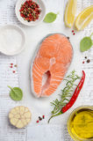 Fresh raw salmon steak with lemon, olive oil and spices on rustic wooden background. Ingredients for making healthy dinner. Health. Y diet concept. Top view Royalty Free Stock Photo