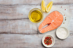 Fresh raw salmon steak with lemon, olive oil and spices on rustic wooden background. Ingredients for making healthy dinner. Healthy diet concept. Top view Stock Photography