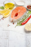 Fresh raw salmon steak with lemon, olive oil and spices on rustic wooden background. Ingredients for making healthy dinner. Healthy diet concept. Selective Stock Photography