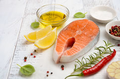 Fresh raw salmon steak with lemon, olive oil and spices on rustic wooden background. Ingredients for making healthy dinner. Healthy diet concept. Selective royalty free stock photography