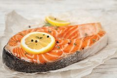 Fresh raw salmon steak with lemon and pepper. On table, closeup Stock Photography