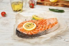 Fresh raw salmon steak with lemon and pepper. On wooden table Stock Photography