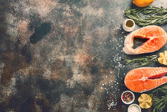 Fresh raw salmon steak. Lemon, rosemary and spices on dark rustic concrete background. Food frame top view with copy space. Ingredients set for making healthy Stock Photo