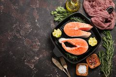 Fresh raw salmon steak. Lemon, rosemary and spices on grill frying pan over dark rustic concrete background, top view with copy space. Ingredients set for Royalty Free Stock Image