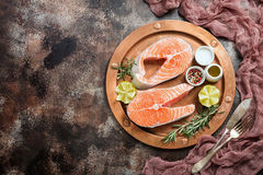 Fresh raw salmon steak. Lemon, rosemary and spices on metal plate over dark rustic concrete background, top view with copy space. Ingredients set for making Stock Images
