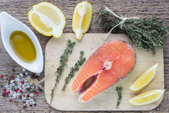 Fresh raw salmon steak. With lemon, thyme and spices on wooden table Royalty Free Stock Photo