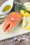 Fresh raw salmon steak. With lemon, thyme and spices on wooden table Royalty Free Stock Images