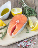 Fresh raw salmon steak. With lemon, thyme and spices on wooden table Stock Images