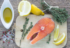 Fresh raw salmon steak. With lemon, thyme and spices on wooden table Royalty Free Stock Photos