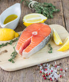 Fresh raw salmon steak. With lemon, thyme and spices on wooden table Stock Image