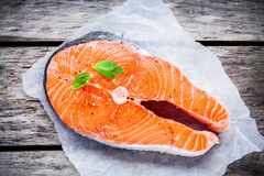 Fresh raw salmon steak on paper with basil Royalty Free Stock Images