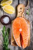Fresh raw salmon steak with salt, lemon, and rasemary. On the rustic wooden table Stock Image