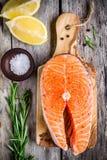 Fresh raw salmon steak with salt, lemon, and rasemary Stock Image