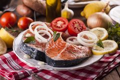 Fresh raw salmon steak. With salt, lemon, and tomato on the rustic wooden table Royalty Free Stock Photo