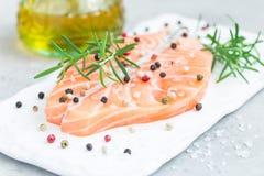 Fresh raw salmon steak with seasonings on board, horizontal. Fresh raw salmon steak with seasonings on white board, horizontal Royalty Free Stock Image