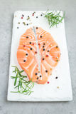 Fresh raw salmon steak with seasonings on board, vertical Royalty Free Stock Photos