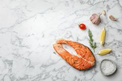 Fresh raw salmon steak and seasonings. On marble background, top view Stock Images