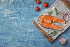Fresh raw salmon steak with seasonings. On wooden background, top view Royalty Free Stock Photography