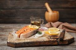 Fresh raw salmon steak with seasonings. On wooden board Stock Image