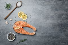 Fresh raw salmon steak with seasonings. On gray background, top view Royalty Free Stock Image
