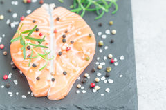 Fresh raw salmon steak with seasonings on stone board, copy space. Fresh raw salmon steak with seasonings on stone board, horizontal, copy space Royalty Free Stock Photos