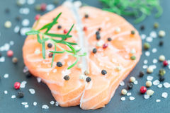 Fresh raw salmon steak with seasonings on stone board, horizontal. Closeup Stock Images