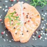 Fresh raw salmon steak with seasonings on stone board, square. Format Royalty Free Stock Photo