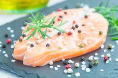 Fresh raw salmon steak with seasonings on stone, horizontal. Fresh raw salmon steak with seasonings on stone board, horizontal Royalty Free Stock Image