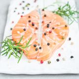 Fresh raw salmon steak with seasonings on white board, square. Format Stock Photos