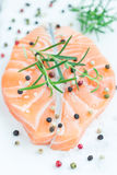 Fresh raw salmon steak with seasonings on white board, vertical Royalty Free Stock Images
