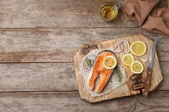 Fresh raw salmon steak with seasonings. On wooden background, top view Royalty Free Stock Image