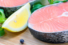 Fresh raw salmon steak and slice of lemon, close up Royalty Free Stock Photos