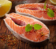 Fresh raw salmon steak slices. On wooden cutting board Stock Images