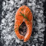 Fresh raw salmon steak with thyme and rosemary on ice. Top view, square image Stock Photos