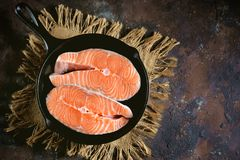 Fresh raw salmon steaks in a cast-iron frying pan. Tasty food Stock Photos