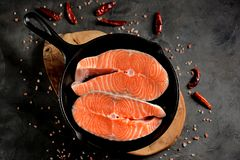 Fresh raw salmon steaks in a cast-iron frying pan. Tasty food Stock Photography