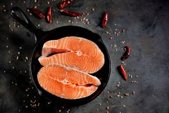 Fresh raw salmon steaks in a cast-iron frying pan. Tasty food Royalty Free Stock Images