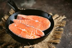 Fresh raw salmon steaks in a cast-iron frying pan. Tasty food Royalty Free Stock Photo