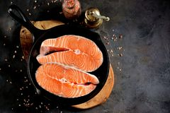 Fresh raw salmon steaks in a cast-iron frying pan. Tasty food Royalty Free Stock Photography